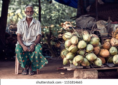 Varkala, Kerala, India – November 30, 2017: Portrait of unidentified Indian man with coconuts. Daily lifestyle in rural area in South India.