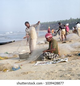 VARKALA, KERALA,INDIA - APRIL 2010: Fishermen removing the catch from their nets early in the morning at Varkala beach, Kerala, India. Shot on (6x6) film.