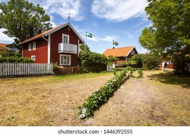 Varmdo, Sweden - June 21, 2019: Finished midsummer pole lies on the ground ready for rising and midsummer celebration on the island of Sandö (Sandhamn) in the Stockholm archipelago.