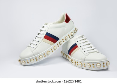 Varna, Bulgaria - 11/05/2018: Gucci Pearl Web low-top sneaker in white leather, glass pearl and gold-toned studs - stylish, fashionable. Fashion concept.
