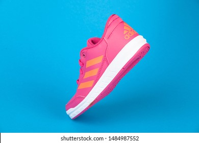 Varna , Bulgaria - AUGUST 13, 2019 : ADIDAS ALTA SPORT pink shoe, on blue background. Product shot. Adidas is a German corporation that designs and manufactures sports shoes, clothing and accessories