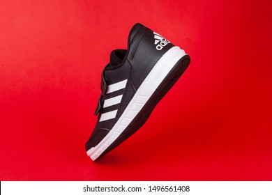 Varna , Bulgaria - AUGUST 13, 2019 : ADIDAS ALTA SPORT shoe, on red background. Product shot. Adidas is a German corporation that designs and manufactures sports shoes, clothing and accessories