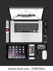Varna, Bulgaria - February 09, 2015: Top view of Apple gadgets technology mockup consisting macbook pro with apple watch web page on the screen, ipad air 2, smart watch concept, iphone 5s, magic mouse