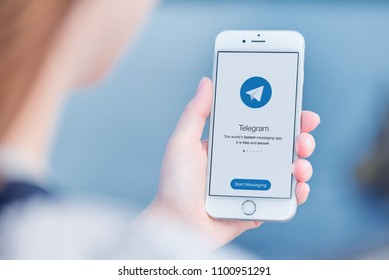 Varna, Bulgaria - January 23, 2018: Telegram messenger on Apple iPhone in woman hands over the shoulder view.