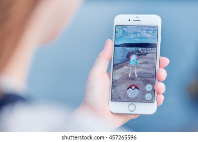 Varna, Bulgaria - Jul 19, 2016: Nintendo Pokemon Go augmented reality mobile application game with Tentacool pokemon catching on Apple iPhone 6S in female hand. Blurred view on the background.