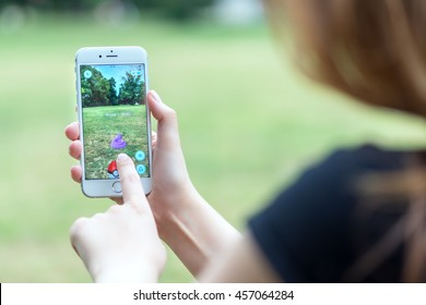Varna, Bulgaria - Jul 20, 2016: Nintendo Pokemon Go augmented reality mobile application game with Ekans pokemon catching on Apple iPhone 6S in female hands.