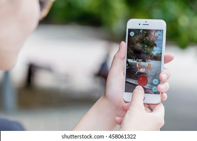 Varna, Bulgaria - Jul 20, 2016: A woman battles Krabby pokemon while playing the Nintendo augmented reality mobile game Pokemon Go on an Apple iPhone 6S.