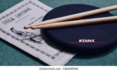 Varna, Bulgaria - July 5th, 2019: Tama drum pad with two drumsticks on it, on a stick control music book as background.