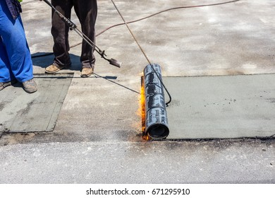 VARNA, BULGARIA - June 20, 2017: workers at construction site install roll of roofing insulation material during repair of waterproofing of bridge. Flame during welding of waterproofing membrane
