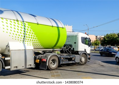 Varna, Bulgaria, June 23, 2019. White truck with a tank for propane or other fuel transportation turns on the main road in the city on a sunny day.