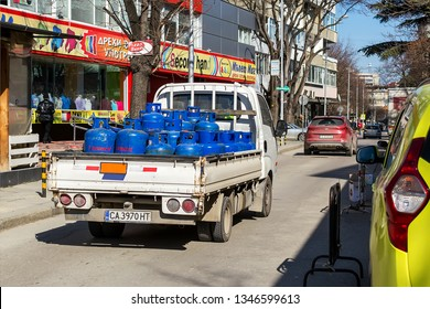 Varna, Bulgaria, March 08, 2019. A small open body truck carries blue cylinders with compressed gas to customers. City delivery of gas cylinders. Real city life.