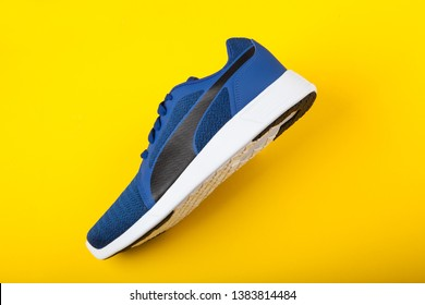 Varna , Bulgaria - MARCH 15, 2019: PUMA ST TRAINER EVO KNIT sport shoe on yellow background. Puma is a German company. PUMA is the third largest sportswear manufacturer in the world. Product shots