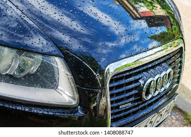 Varna, Bulgaria, May 25, 2019. Audi car grille with chrome logo and front hood with drops of rain and reflection of sky and street.