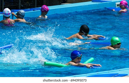 VARNA, BULGARIA - May 31, 2017: Charming happy children enjoy bathing with children's swimming pool. Coach teaches swimming children in pool. Sports children. Children's sports