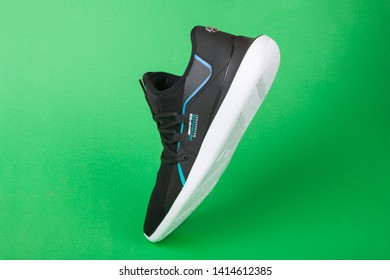 Varna , Bulgaria - MAY 8, 2019: PUMA AMG MERCEDES EVO CAT RACER sport shoe on green background. Puma is a German company. PUMA is the third largest sportswear manufacturer in the world. Product shot
