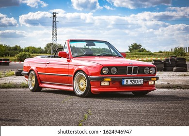 Varna, Bulgaria - September 25, 2018: BMW M3 E30 cabrio on race track ready to drift. LED headlights. Classic retro car. Old school. Wide fenders and BBS forged rims. Beautiful cloudy blue sky