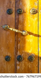 Varnished heavy wooden front door with brass handle and studs