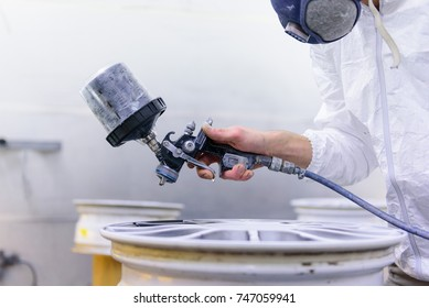 A varnisher is painting an alloy rim of a car with a spray gun. No face but dust mask