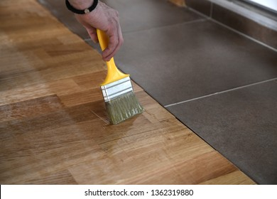 Varnishing lacquering parquet floor by paintbrush - second layer. Home renovation parquet. Varnish paintbrush strokes on a wooden parquet. Application of a highly glossy parquet lacquer