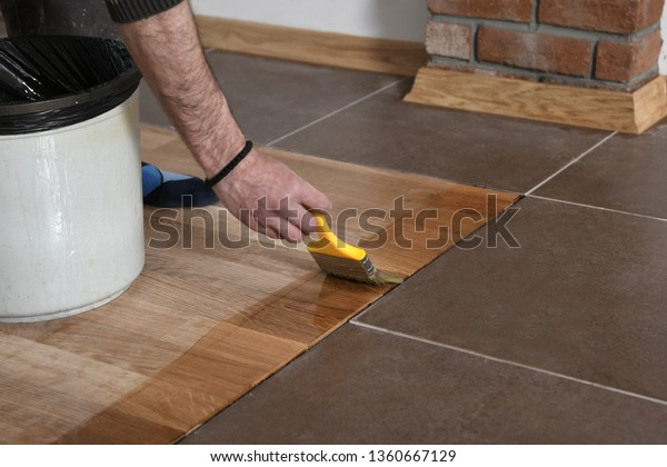 Varnishing Lacquering Parquet Floor By Paintbrush Stock Photo