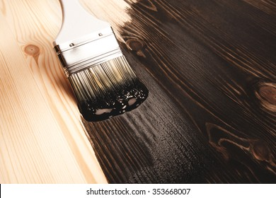 Varnishing natural wood with paint brush in brown color.
