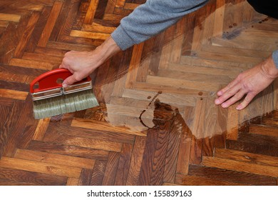 Varnishing of oak parquet floor, workers hand and brush