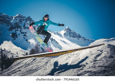 Vars city, Vars province/France, 6- April-2017 : French Alps winter. Tourist jumping on snowboard testing snowpark during sunny day.