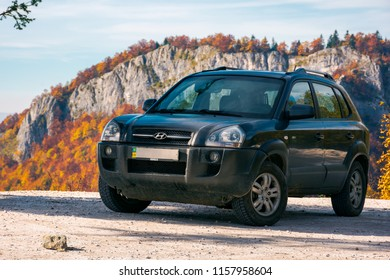 Vartop, Romania - OCT 15, 2017: Hyundai Tucson SUV on the road in mountains. rocky cliffs in colorful reddish foliage in the distance. beautiful autumn scenery. travel europe by car concept