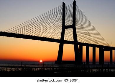 Vasco da Gama bridge, backlit by a mid June sunrise, at Lisbon, Portugal. Image unsharpened.