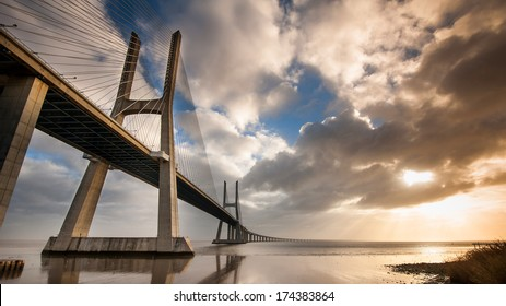 Vasco da Gama Bridge over the Tagus river at sunrise with cloudy sky. Lisbon, Portugal. It is the longest bridge in Europe (including viaducts), with a total length of 17.2 km (10.7 mi).