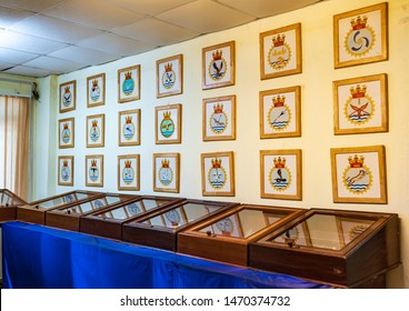 Vasco da Gama, Goa, India - 03/09/2019: Indian navy emblems in a wooden frame for different battalions of soldiers displayed on a white wall in a interior room at the naval aviation museum.