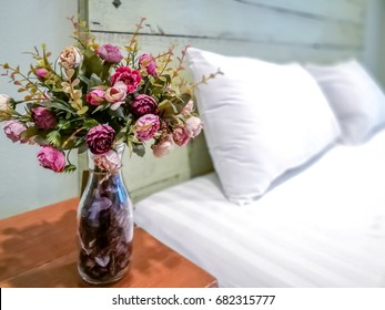 Vase of artificial flower decoration on wooden table in modern rustic Bedroom