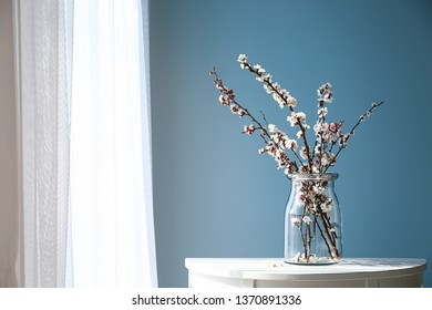 Vase with beautiful blossoming branches on table near window