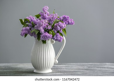 Vase with beautiful blossoming lilac on table against grey background