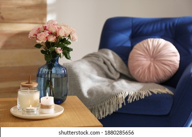 Vase with beautiful flowers and burning candles on wooden table indoors, space for text. Interior elements