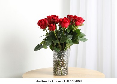 Vase with bouquet of red roses on wooden table, space for text