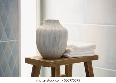 Vase ceramic pot and white cotton towels on a wooden chair inside a bright bathroom