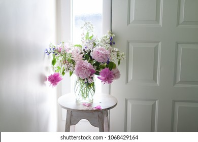 A vase of colorful pink and purple flowers sits on a white pedestal next to a window and door. The flowers are fresh, blooming, large, and beautiful.