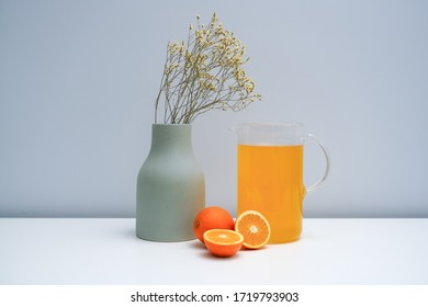 A vase with dried flowers and a glass of orange juice on the white table.
