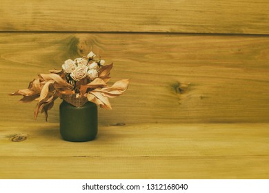 Vase with dried flowers on wooden table.Toned photo.