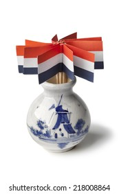 Vase with dutch flags cocktail sticks on white background