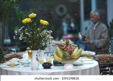 Vase with flowers on the table with food, drinks and fruits in a Vietnamese restaurant