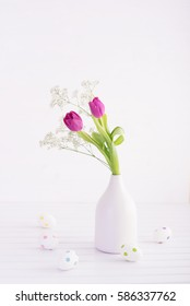 Vase of fresh tulips with decorative easter eggs on wooden table. High key