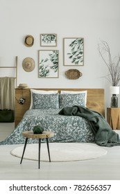 Vase on wooden stool in bright green bedroom with posters above a king-size bed with wooden bedhead