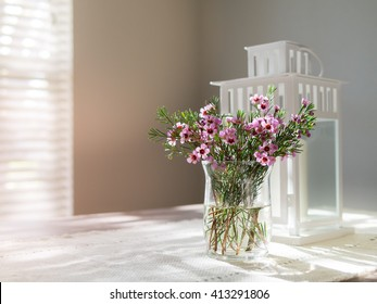 Vase of pink flowers and greens on wood table with runner, white lamp in the background