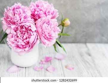 Vase with pink peony flowers on a white wooden table