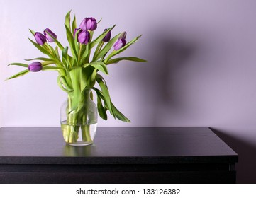 Vase with purple tulips on black table with lilac walls