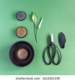 Vase and tools for creating ikebana: different size kenzenas and Japanese scissors on a green background