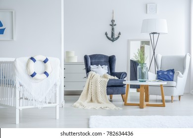 Vase with white flowers standing on a small table in bright bedroom for a toddler in marine style