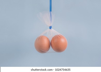 Vasectomy concept two eggs in a tulle bag with blue ribbon on a blue background